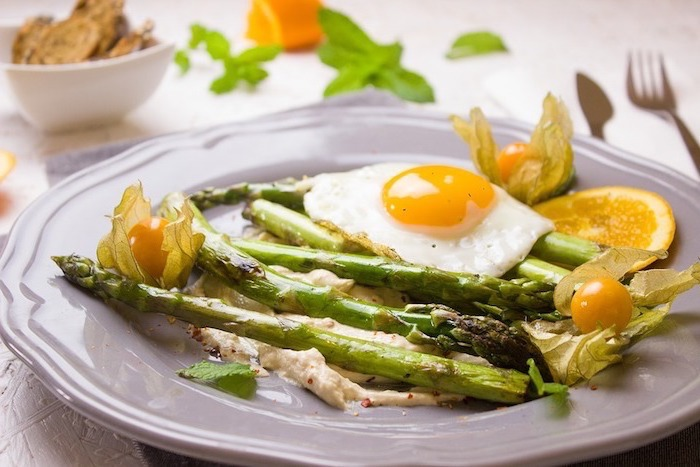 white plate, asparagus and an egg, with cherry tomatoes, lemon slices, balanced diet