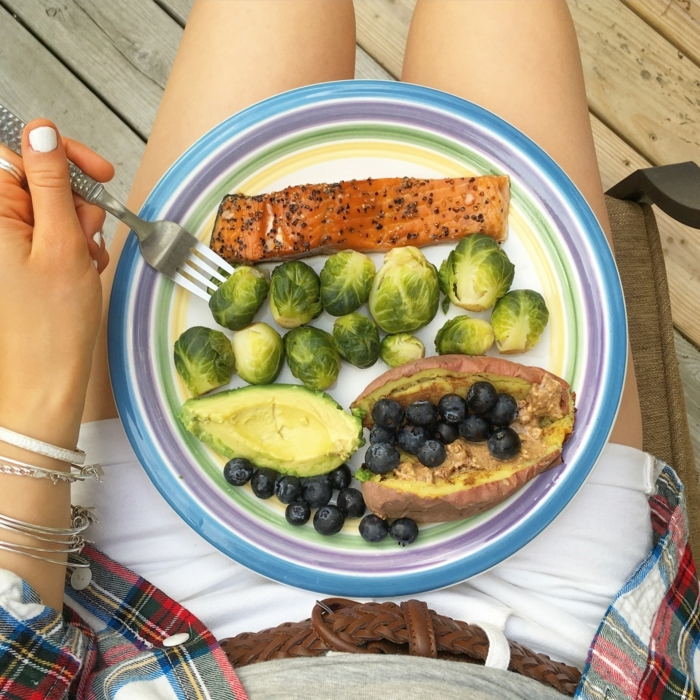 woman holding a plate, full of fish fillet, avocado and blackberries, balanced diet, white jean shorts
