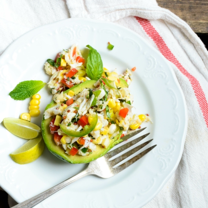 avocado salad, with corn and meat, basil and lemon slices on the side, healthy eating plans, in a white plate