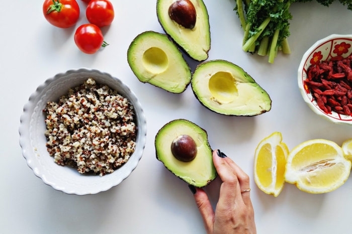 sliced avocados, quinoa salad, in a white bowl, slices of lemon around, balanced diet, bowl of goji berry