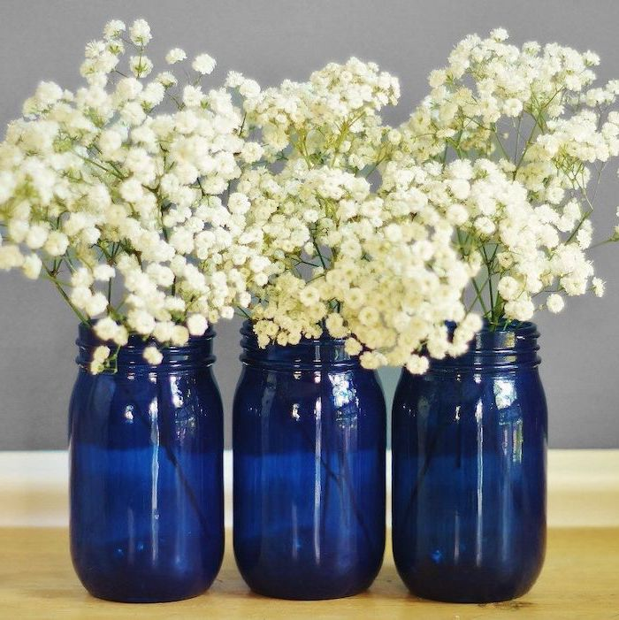 three mason jars, painted in blue, filled with white flowers, kitchen table centerpieces, wooden table