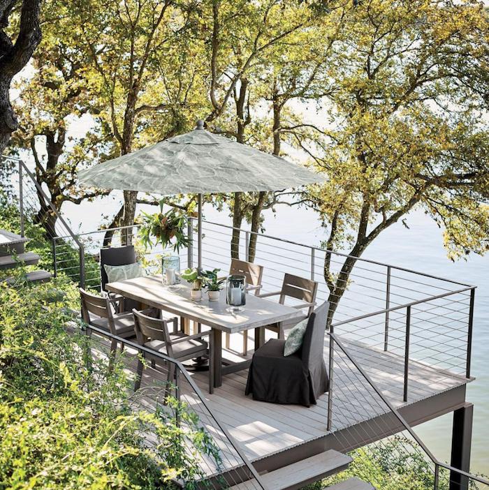 balcony overlooking a river, wooden garden furniture, large umbrella, staircase leading to the balcony, backyard garden ideas