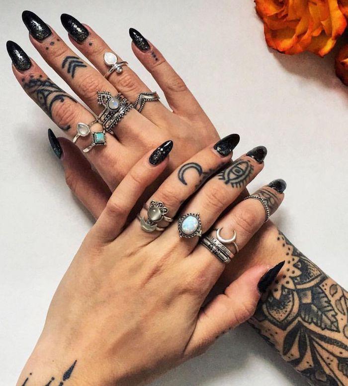 long black nails, many silver rings, mandala tattoos on both hands, ring finger tattoos