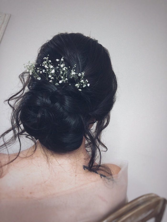 white background, small flowers hair accessory, wedding hairstyles for long hair, black hair in a low updo