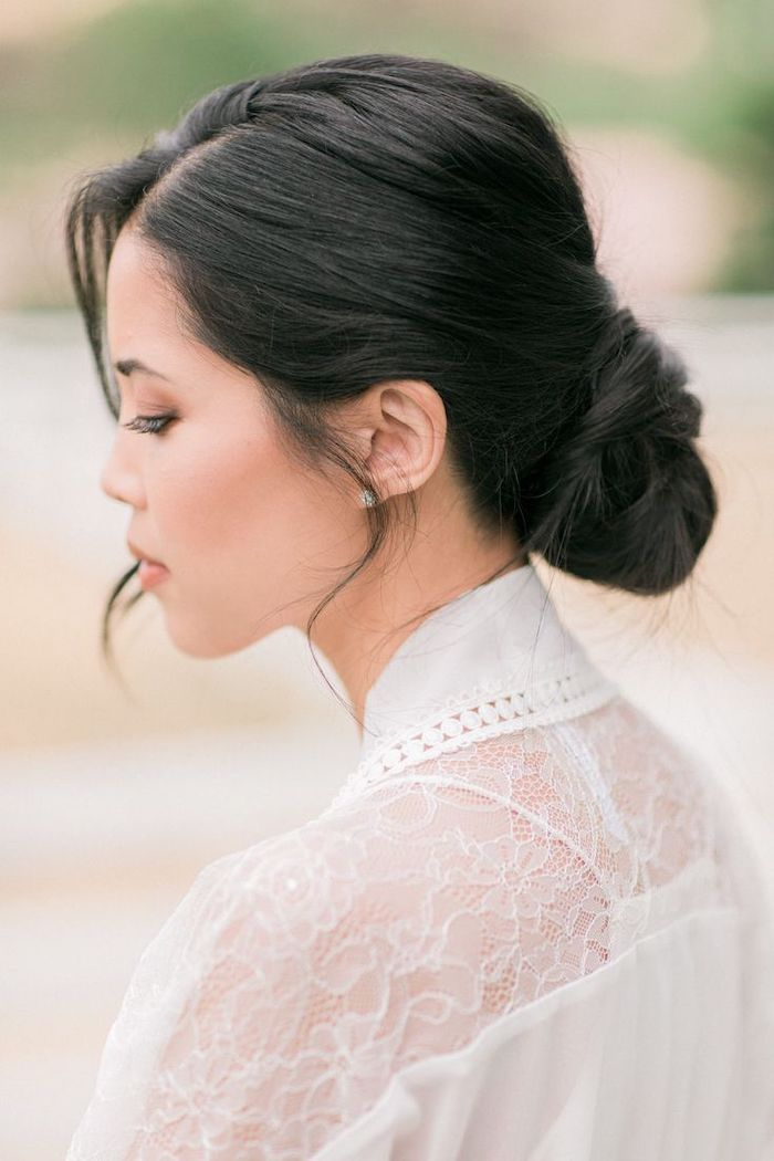 black hair, in a low updo, wedding hairstyles for long hair, white dress with lace