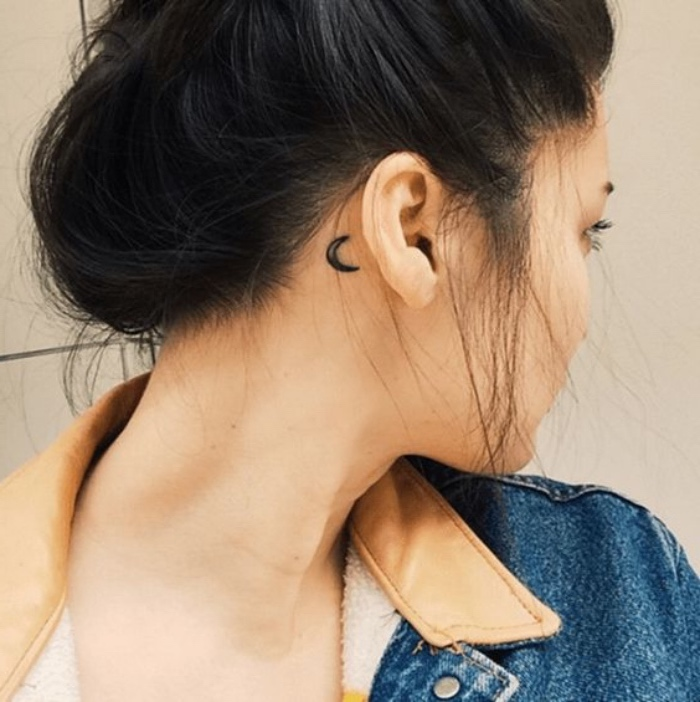 crescent moon behind the ear tattoo, small tattoos for women, black hair in a messy bun, jean jacket
