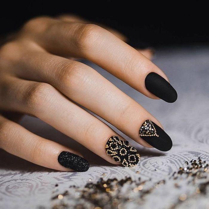 nail designs, black matte nail polish, many little stones and crystals, on two nails, black glitter nail polish