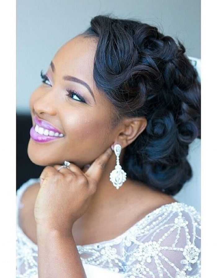black curly hair, in a low updo, wedding hairstyles for long hair, white lace dress, diamond earrings