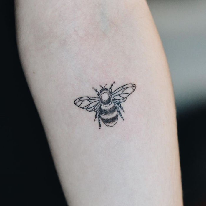 small black and white bee, forearm tattoo, geometric tattoo sleeve, blurred background