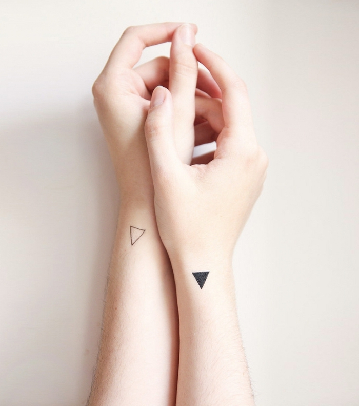 a set of hands, small black and white triangles, on both hands, white background, geometric tattoo sleeve