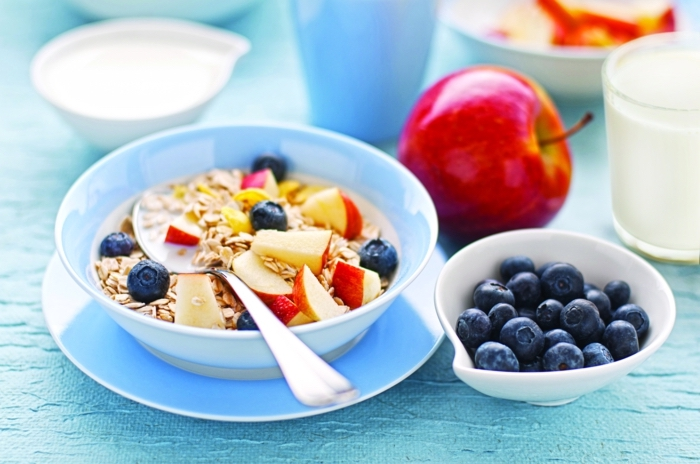 yogurt with oats, apples and blackberries, inside a blue bowl, healthy weekly meal plan, on a blue plate
