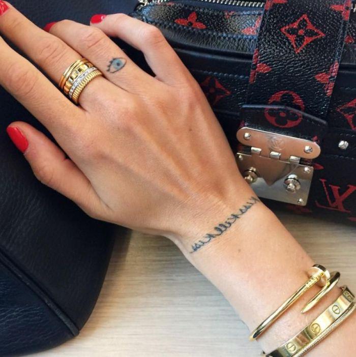 red nail polish, blue eye tattoo, on her ring finger, finger tattoos, golden rings and bracelets