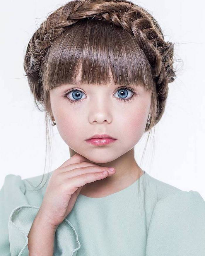 large blue eyes, braided brown hair with bangs, green top, white background, little girl hairstyles