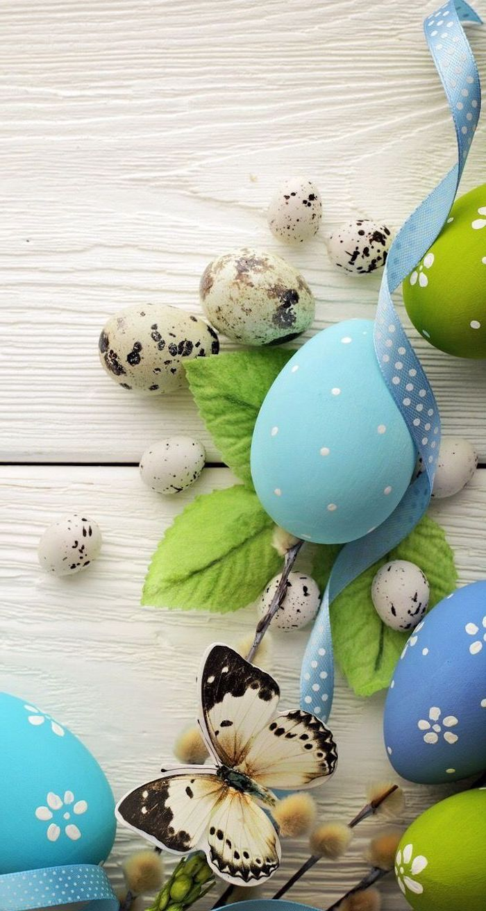 wooden background, green and blue eggs, butterfly and leaves, shaving cream easter eggs