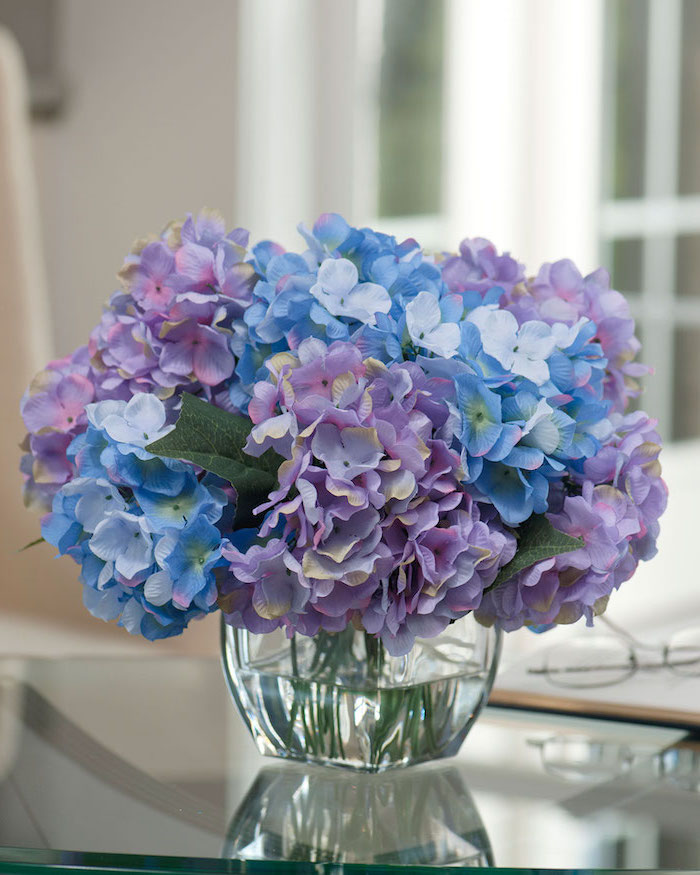 purple and blue flowers, small flower bouquet, flower arrangements, small square glass vase, on a glass table