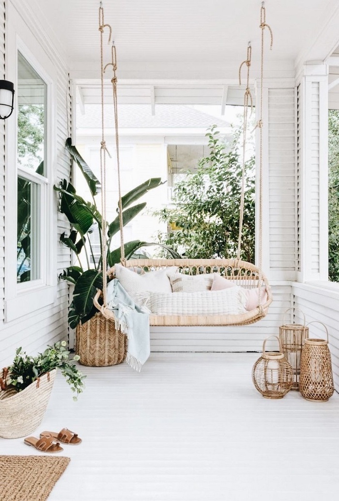 backyard garden ideas, boho style patio, swing with throw pillows, small lanterns, on a white wooden floor