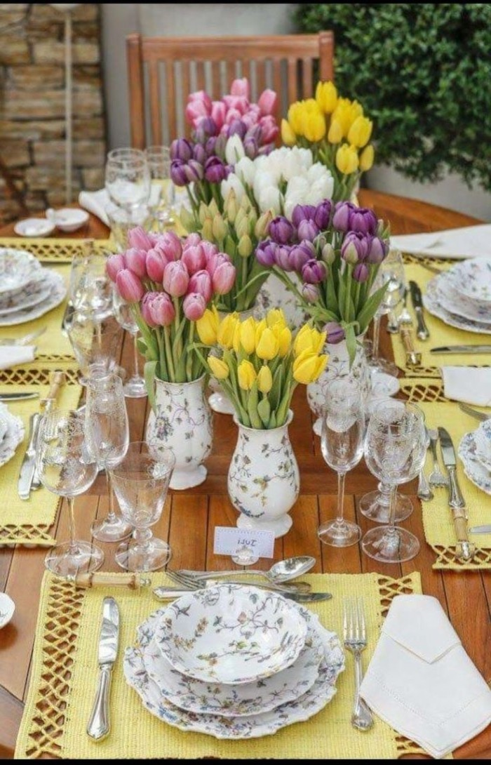 vases full of tilips bouquets, colourful plate settings, simple table decorations, tall wine glasses