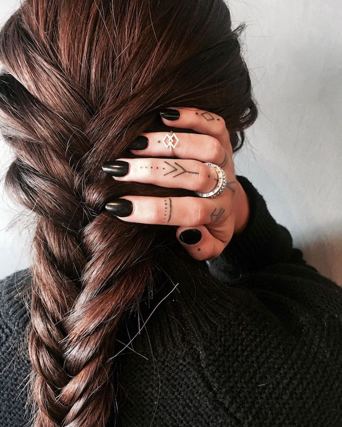 long brown braided hair, hand with many finger tattoos, ring finger tattoos, black nail polish