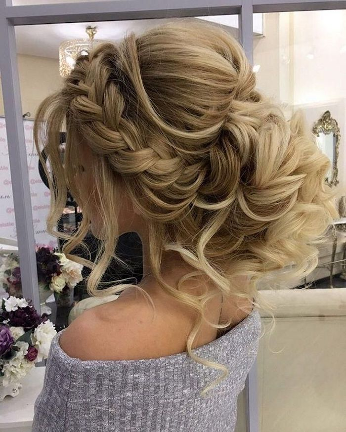 long blonde hair, in a braided updo, wedding hairstyles updo, grey sweater, flower bouquets on the table
