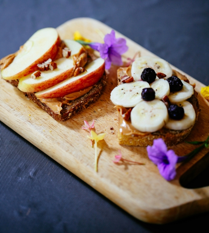wooden cutting board, slices of bread on top, what should i eat for lunch, apple and banana slices
