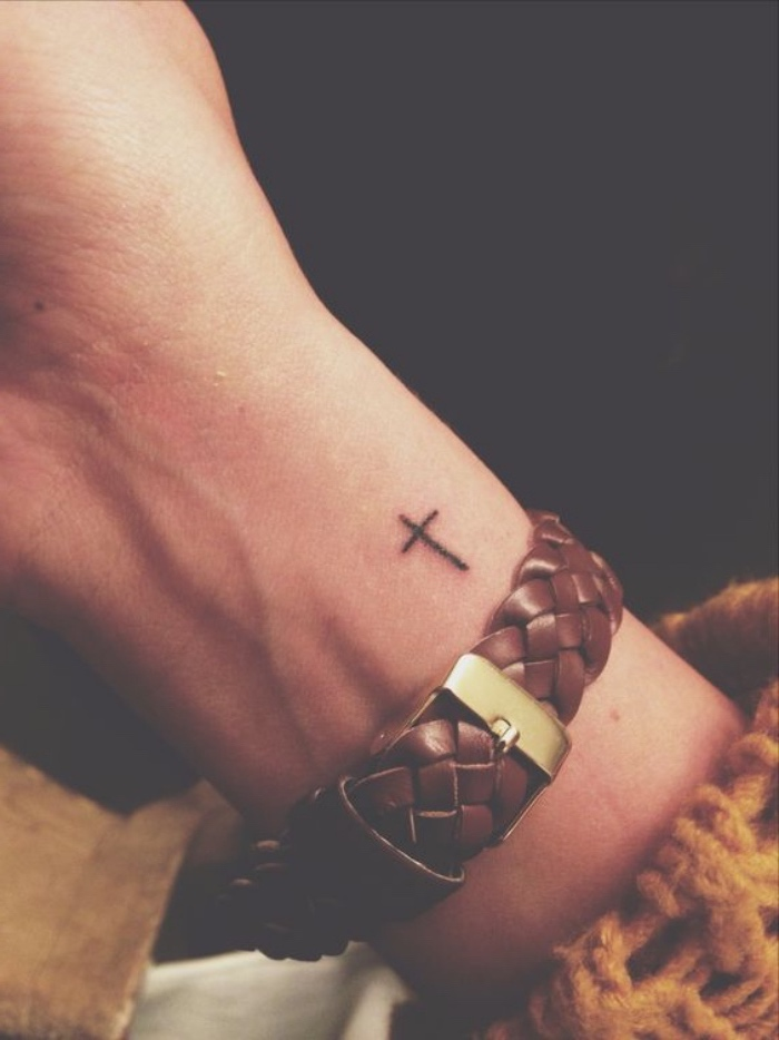 small cross wrist tattoo, small tattoos for women, black leather watch strap, black background
