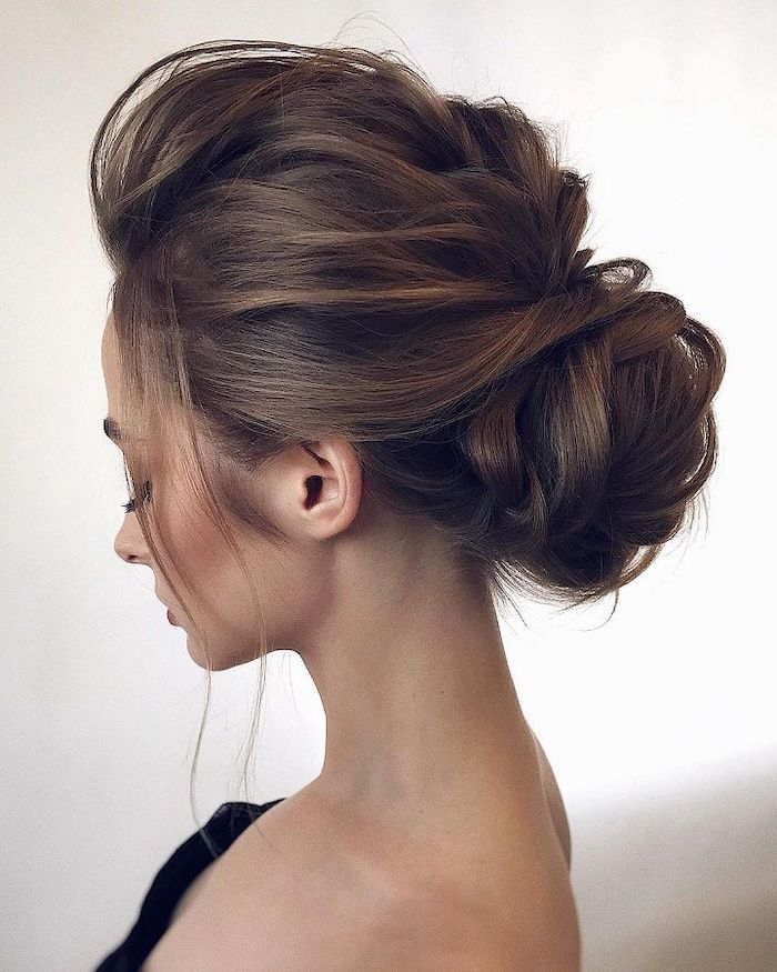 bridal updos, long brown hair, in a low updo, white background, black top, long lashes