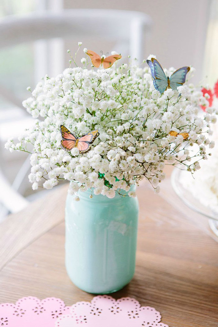 mason jar, painted in light blue, filled with white flowers, small butterfly decorations, floral centerpieces