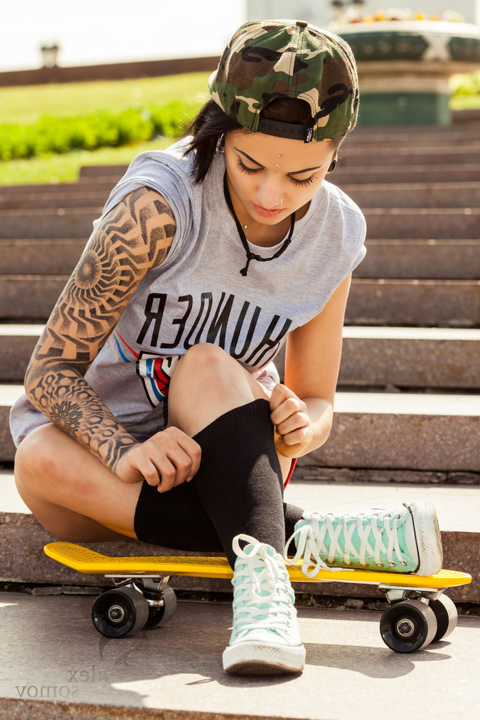 geometric tattoo sleeve, turquoise sneakers, camouflage cap, skateboard girl