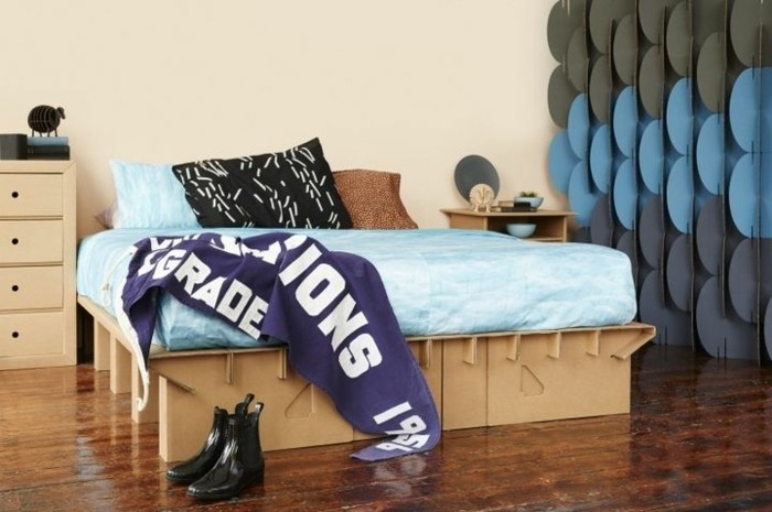 cardboard bed, with blue linens, on a wooden floor, cardboard dresser, cardboard night stand