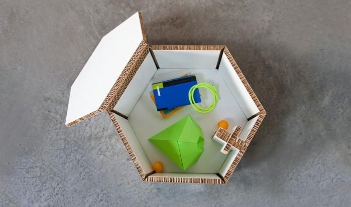 grey cement floor, cardboard box, with a lid, full of toys, cardboard dresser