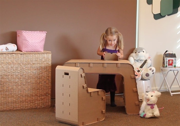 children's room, cardboard dresser, cardboard desk and chair, plush toys, beige wall in the background, furniture made of cardboard
