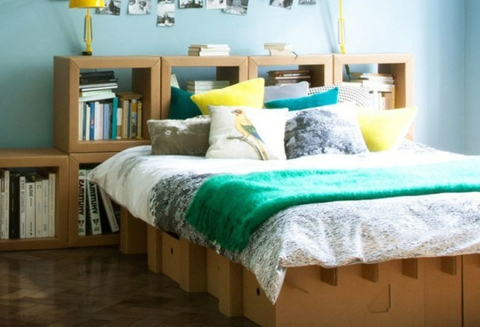 cardboard bed, cardboard shelves, lots of books, green blanket, blue and yellow throw pillows