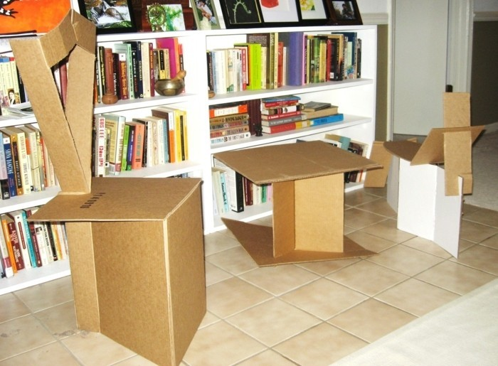 cardboard chairs and table, cardboard shelves, beige tiled floor, large white bookshelf, lots of books