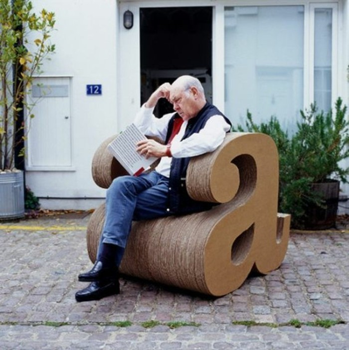 man sitting, on a cardboard armchair, in the shape of the letter a, how to make cardboard