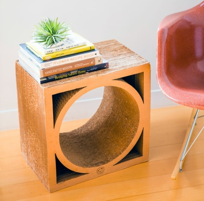 cardboard night stand, with books on it, how to make cardboard, red chair, on a wooden floor