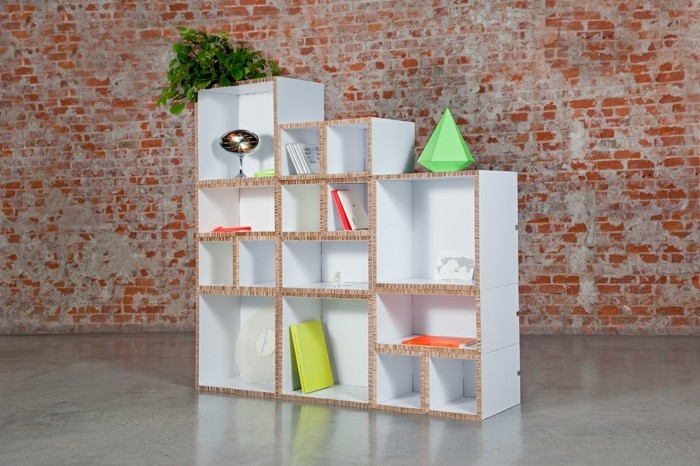 large cardboard bookshelf, painted in white, cardboard furniture diy, in front of a brick wall