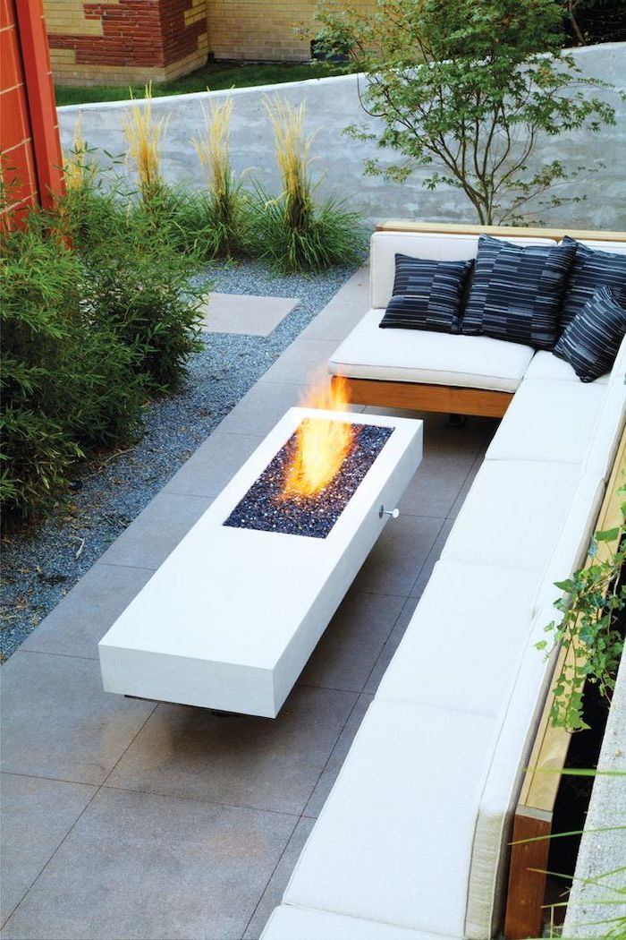 cement table, with a small fire pit, garden decoration ideas, corner sofa, with black throw pillows, planted bushes