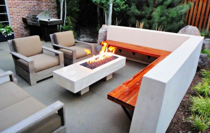small cement table, with a fire pit, wooden bench, garden furniture, garden decoration ideas, planted bushes and trees