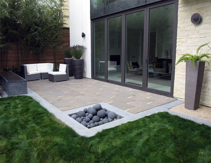 patch of grass, around a cement tiled floor, garden decoration ideas, garden furniture, potted plants