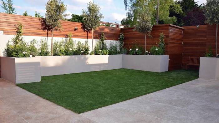 patch of grass, surrounded by cement tiles, planted bushes and trees, garden decoration ideas