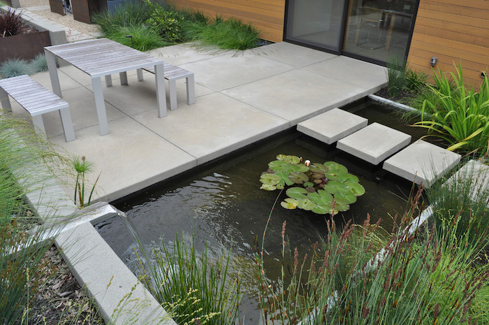 cement tiles, over a small pond, small backyard landscaping ideas, small garden furniture, planted bushes around