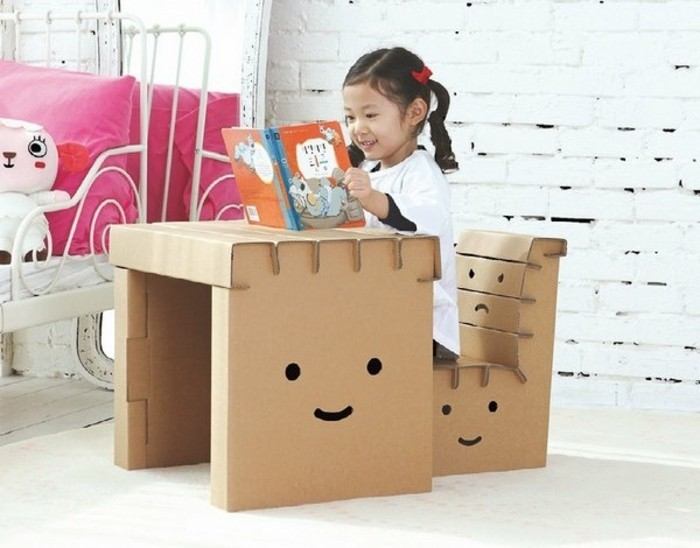 little girl reading, cardboard chair design, children's desk and chair, in front of a white brick wall