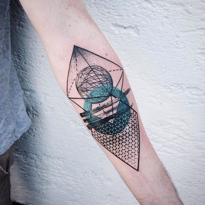 person standing in front of a white wall, geometric tattoo, circles and triangles on the forearm