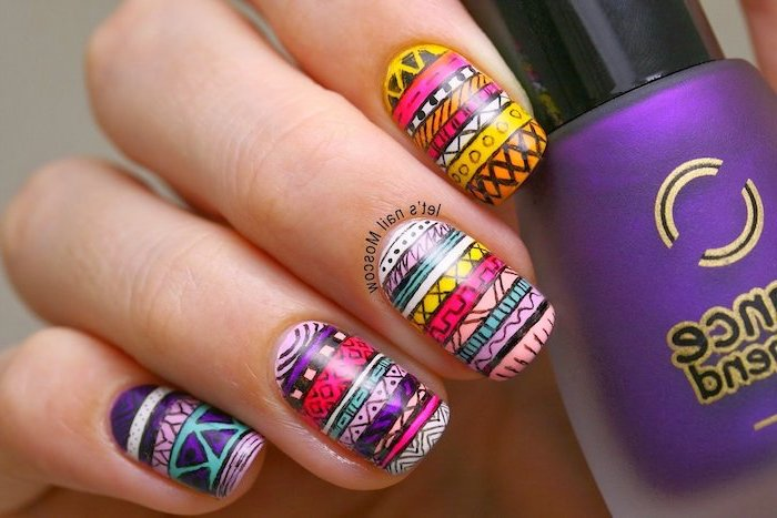 colourful patterned manicure, purple nail polish bottle, simple nail designs, hand holding the bottle
