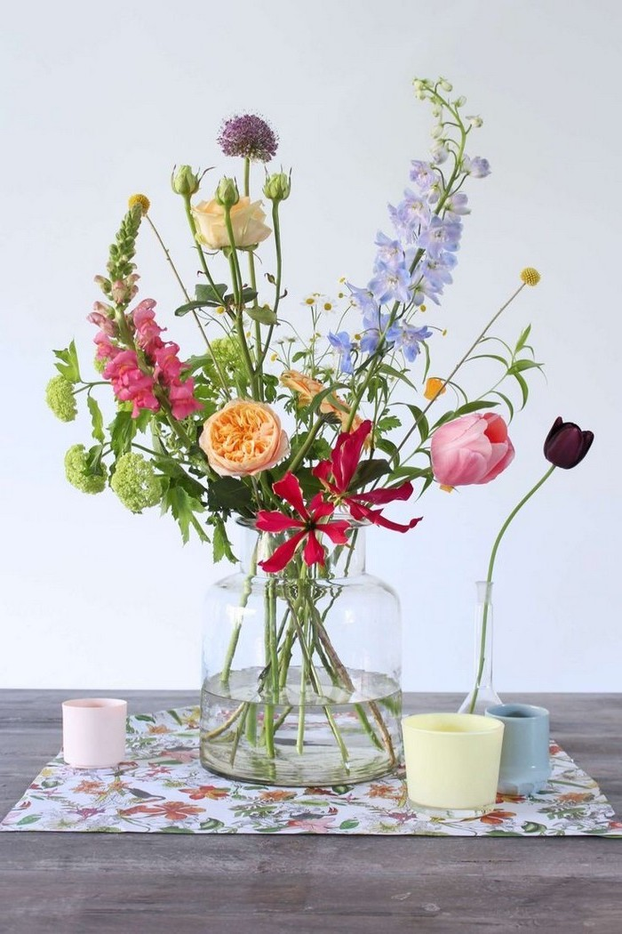 large glass vase, colourful flower bouquet, floral centerpieces, on a wooden table, in front of a white background