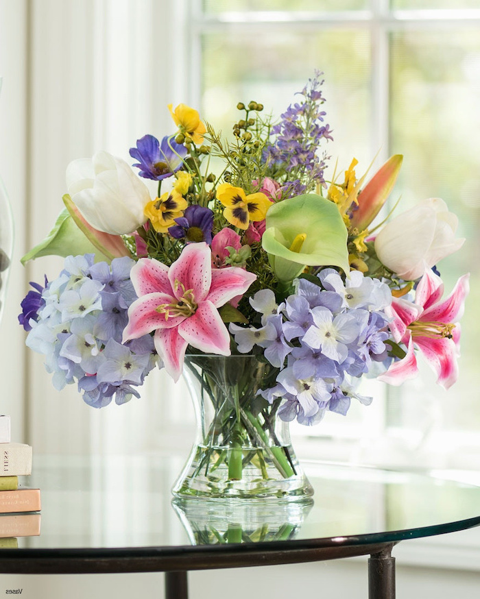 colourful flower bouquet, filled with different flowers, flower arrangements, glass vase on a glass table