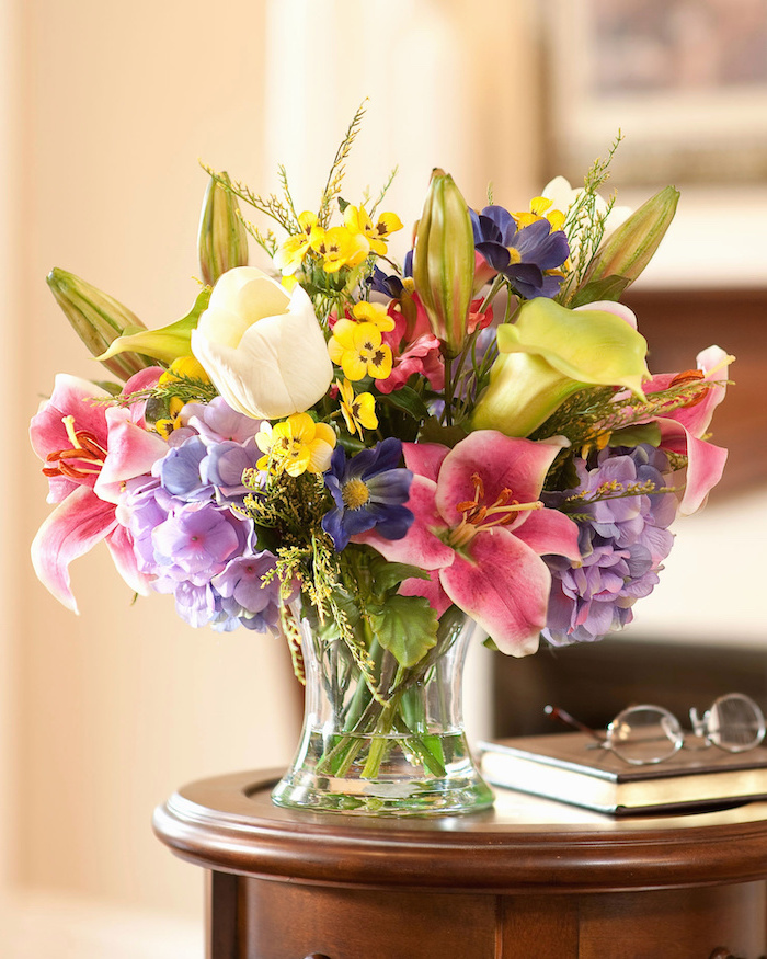 colourful flower, small flower bouquet, on a small wooden table, floral centerpieces, next to glasses and a book