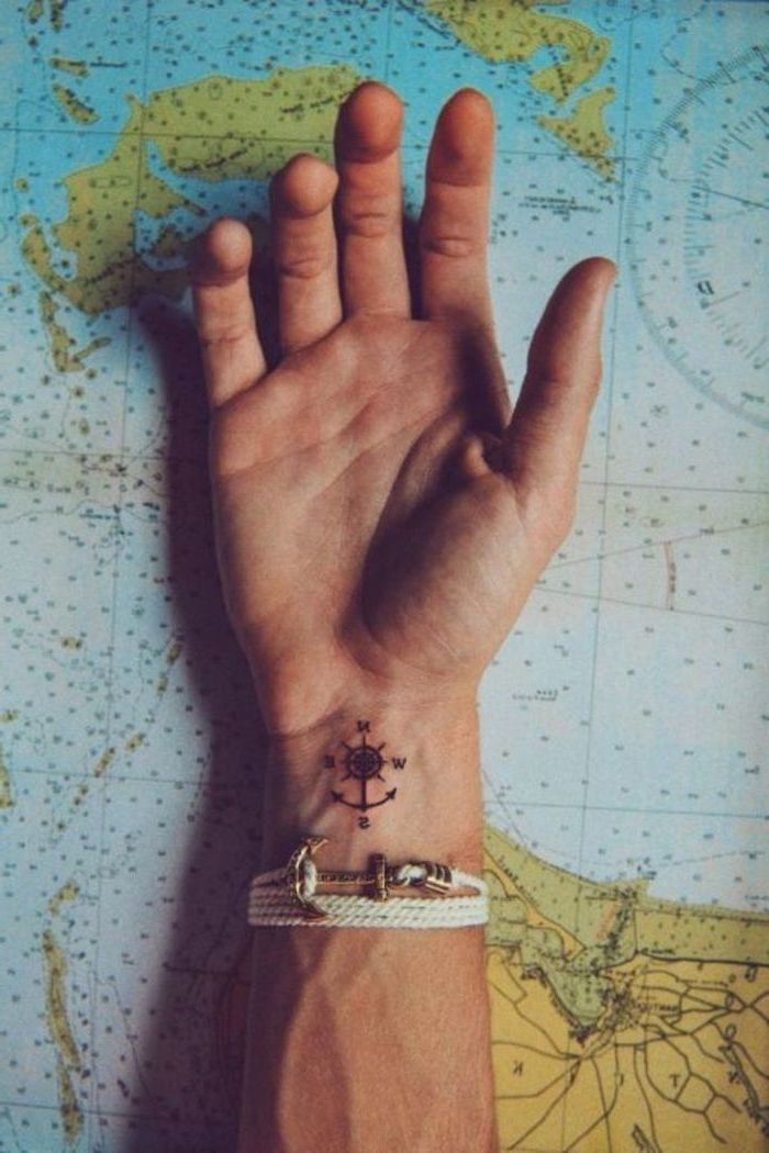 small compass, wrist tattoo, tattoos for men with meaning, hand on top of a map, white anchor bracelet