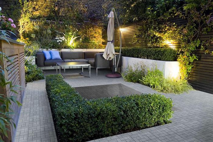 corner sofa, with blue throw pillows, surrounded by short hedges, small backyard landscaping ideas, planted trees