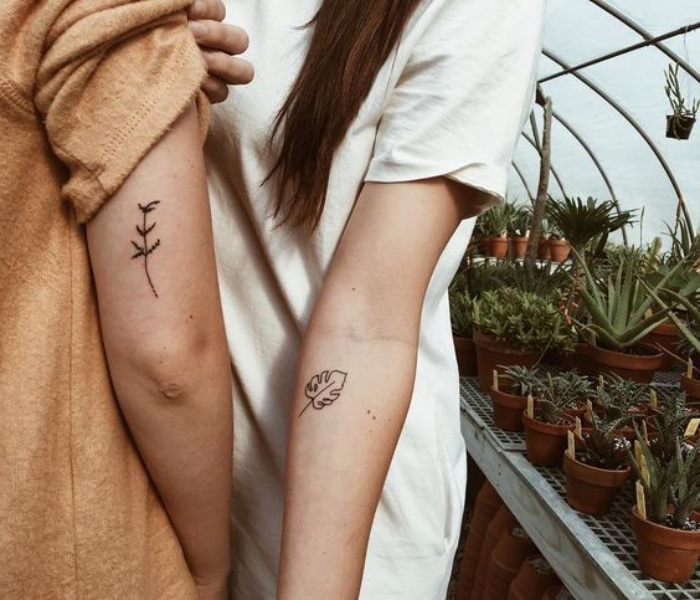 couples matching tattoos, nature inspired, small tattoos, lots of potted plants in the background